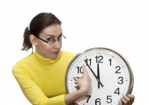 Portrait of an attractive beautiful pretty cute young brown haired caucasian woman (lady, girl, female, person, model) in glasses (spectacles, specs) who is pointing at the clock that shows five to twelve. It's an allegory of the time, appointment, delay, being late, start or finish. Isolated on white background.