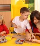 teacher and three preschoolers plazing with wooden blocks