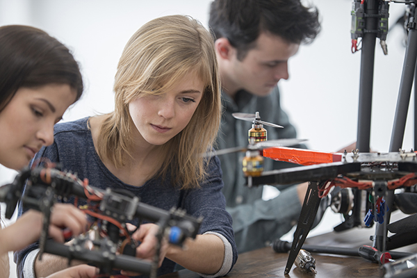 University students at a tech college working on robotic drones as part of their science project.