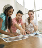 A multi-ethnic group of business professionals are looking over pictures in the boardroom.