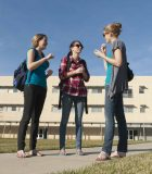 Three girls on school campus having a discussion in sign language