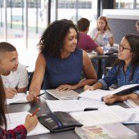 iStock_Teacher_helping_students_studying_books-1200pxW