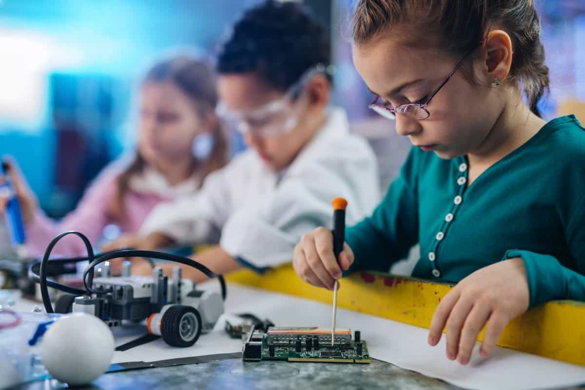 Group of kids working in laboratory. Focus is on small girl repairing computer part.