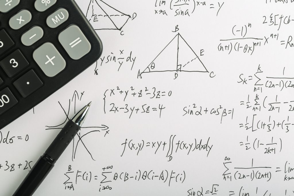 Closeup shot of complex math formulas on paper with calculator and ball pen aside.