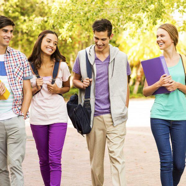 Happy multi-ethnic group of teenage students walking together on university campus. Horizontal shot.
