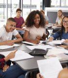 High school kids looking to teacher sitting at their desk