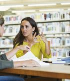 Graduate school or continuing education:  Mid adult women (30s) and young African American man (20s) meeting and studying together in the library, having a serious discussion.