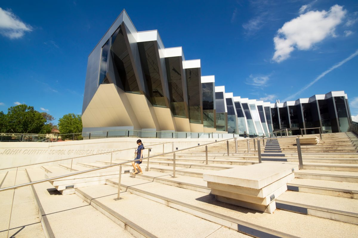Canberra, Australia - March 14, 2014: A woman walks down steps before the John Curtin School of Medical Research at the Australian National University.