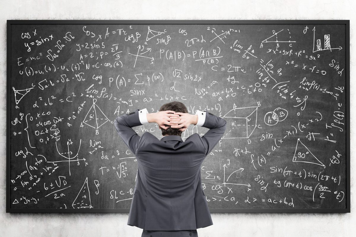 Rear view of a businessman standing with his hands behind his head and looking at formulas on a blackboard.