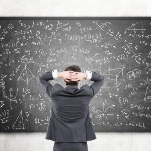 Businessman looking at formulas at blackboard
