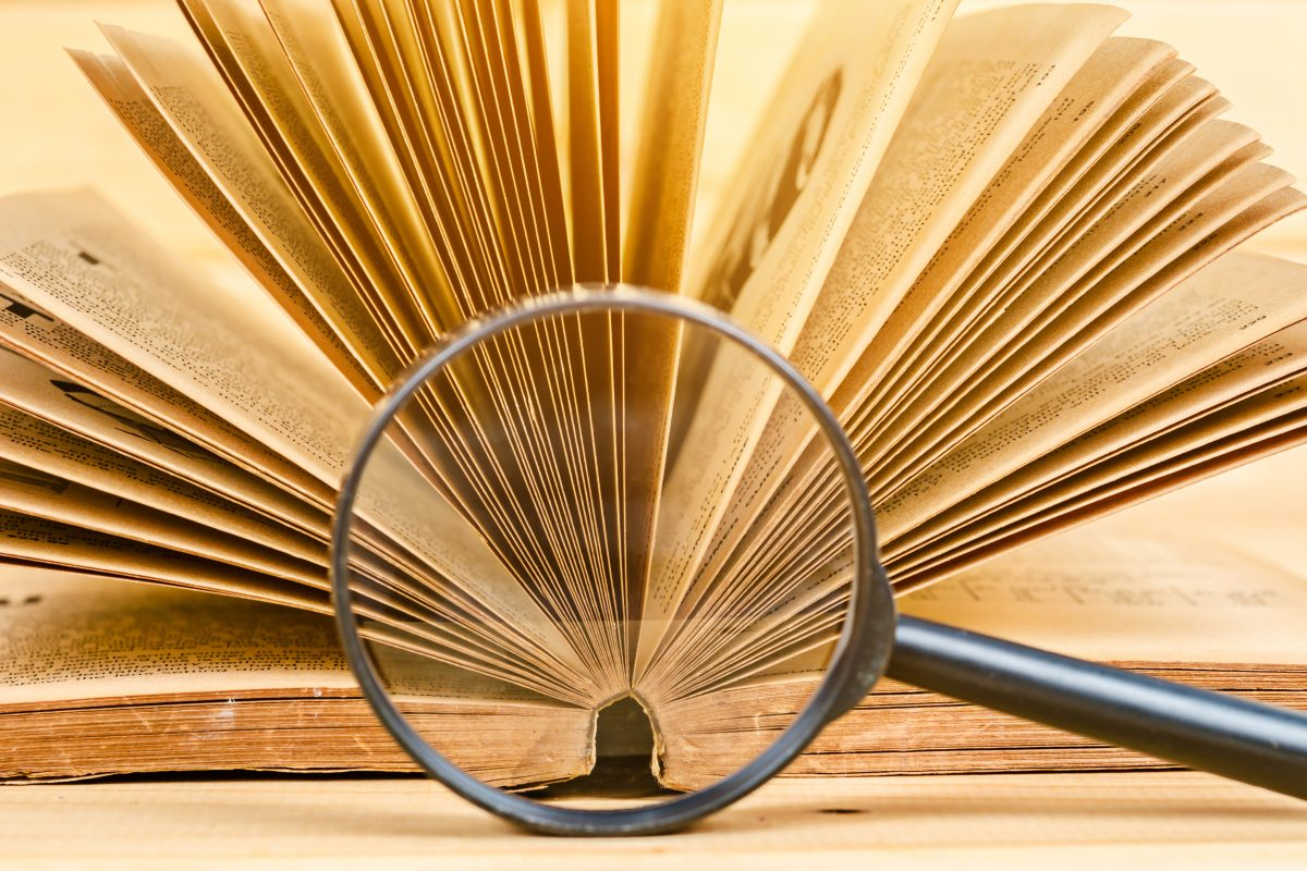 magnifying glass and old book on wood background.
