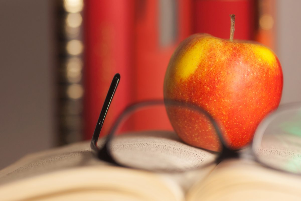 Apple laying on a Book with glasses. Short focus picture.