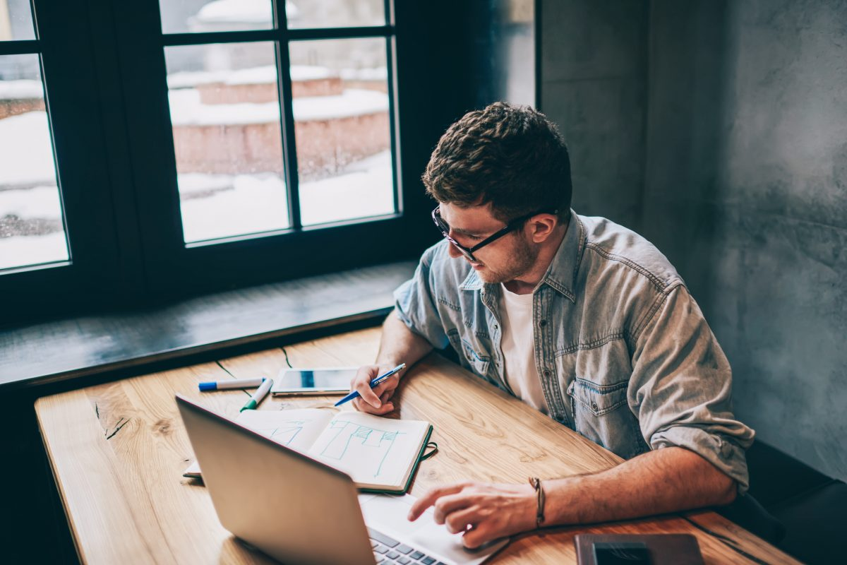 Hipster guy pondering on idea for essay sitting at wooden table with laptop device and looking on textbook, smart male freelancer spending time for distance job thinking about business indoors