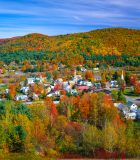 Fall colors surround a country village and church nestled in the hillside of the Green Mountains. A row of mixed hardwood trees fills the foreground leading back to the village of South Royalton and the rolling hills beyond, Vermont