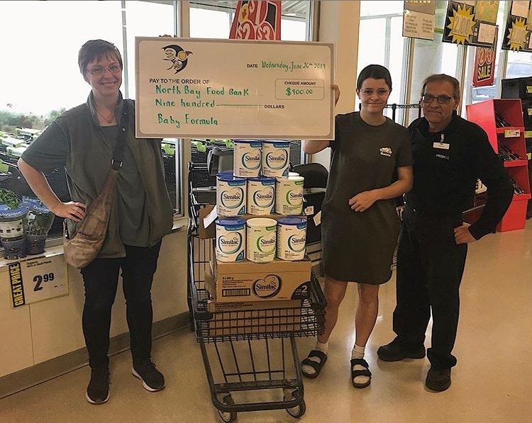 Maeve entregando un cheque de CAD 900 al banco de alimentos de North Bay. El dinero se recaudó con el proyecto Art Battle for Babies.