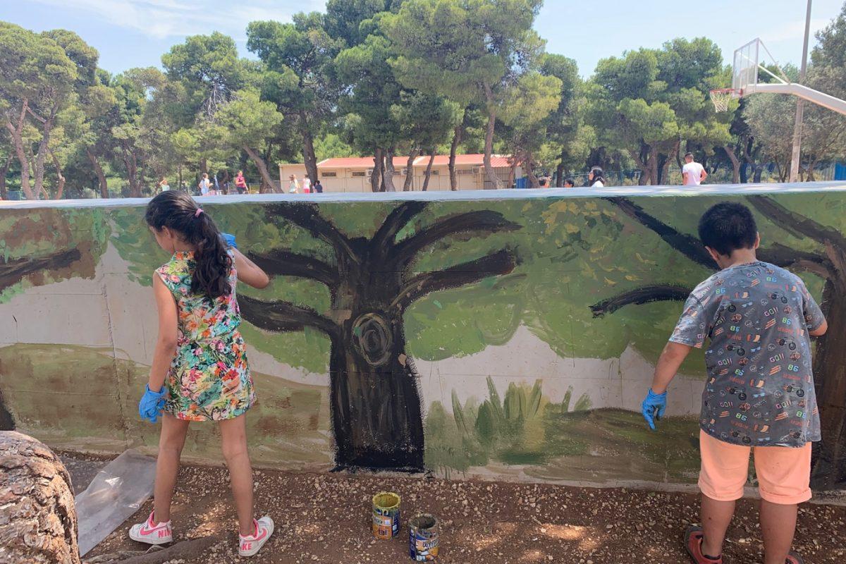 Des élèves peignent la fresque sur le mur situé derrière les gradins du terrain de basketball.