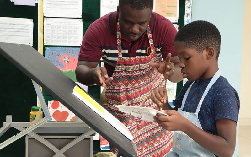 Felix teaching one of his students how to paint during Visual Arts class.