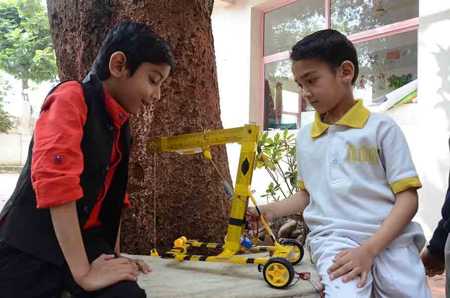 Des élèves utilisent une grue qu'ils ont conçue.