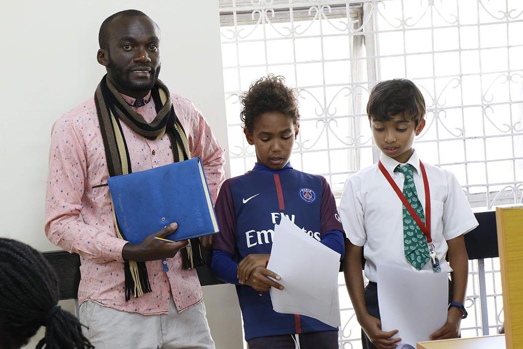Timoteo Ombati, lauréat de la bourse University of the People et enseignant du Programme d'éducation intermédiaire (PEI), entouré de ses élèves.