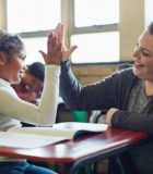 Shot of a young girl giving her teacher a high five in a classroom