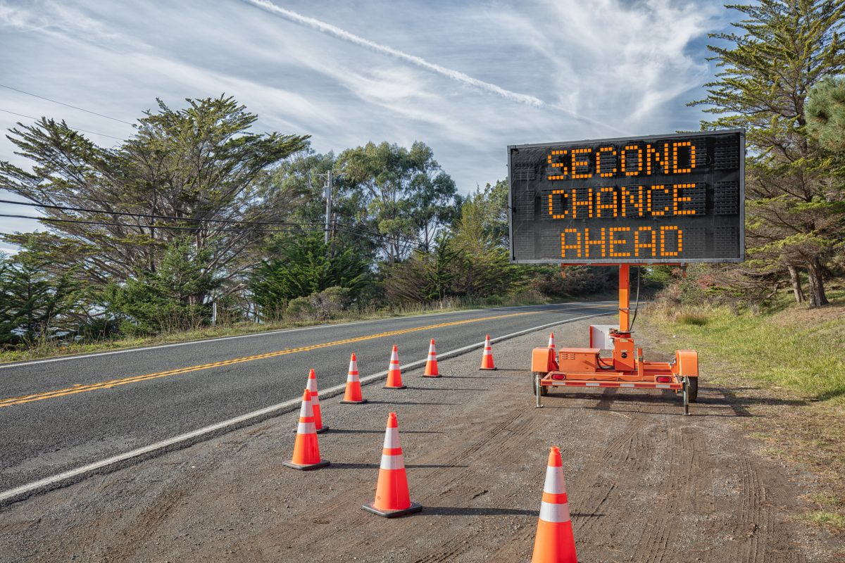 SECOND CHANCE AHEAD: This is a photograph of a mobile roadside sign parked on highway one in northern California. It is a trailer and powered by batteries and provides information and warnings for drivers by displaying words on a large panel display.