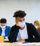 Multiethnic group of students wearing N95 Face masks sitting at the desks in the classroom at the university, keeping distance, having an exam.