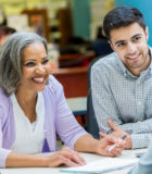 Confident African American senior businesswoman discusses something with colleagues during weekly meeting.
