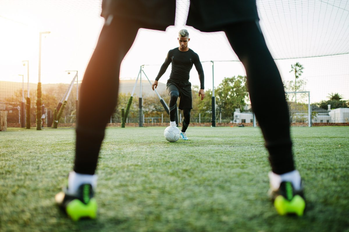 Young soccer players training in football field. Football team practicing on soccer pitch outdoors.